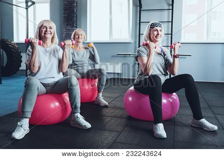 Full Of Energy And Joy. Focused Senior Female Friends Smiling While Taking An Exercise Class And Tra