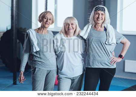 Will You Join Us. Team Of Senior Female Friends In Sportswear Grinning Broadly Into The Camera While