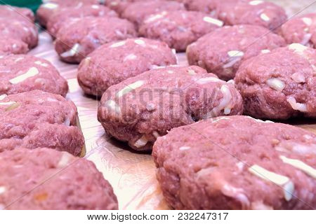 Several Fresh Cutlets Of Meat, Beef, Pork Lie On The Board In Several Rows. In Cutlets Added Cabbage