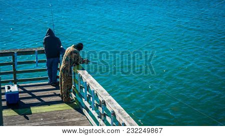 2 Men Fishing On A Pier With Fishing Poles And Cooler