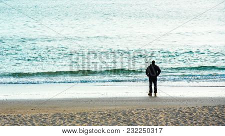 Man Standing On Sandy Beach Fishing With Fishing Pole