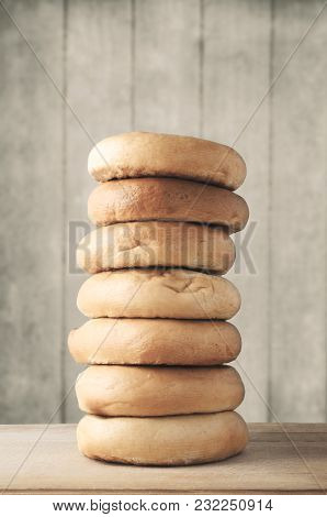Tall Stack Of Bagels On Wood With Planked Background - Filtered