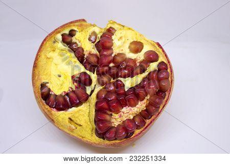 Half Of Ripe Pomegranate On White Background