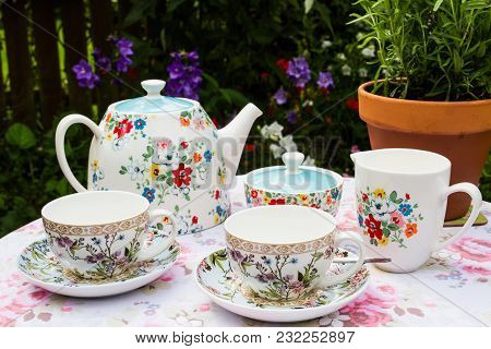 A Floral Tea Service With Teapot, Cups And Saucers And Milk Jug Outdoors In An English Country Garde