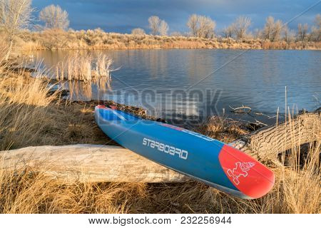 Fort Collins, CO, USA - March 19, 2018: Racing stand up paddleboard on a lake shore - 2018 model of All Star SUP by Starboard.