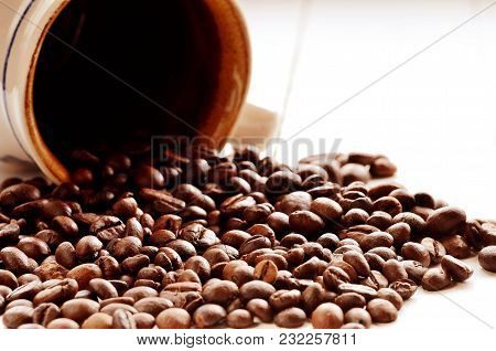 Spilled Coffee Beans From Brown Ceramic Mug On White Wood Planks