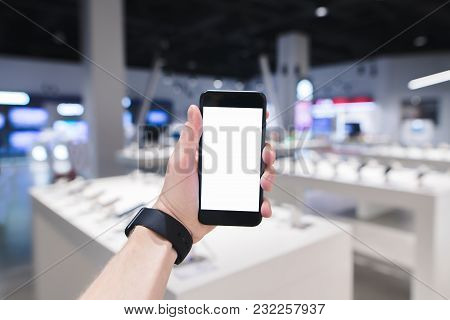A Clock Hand Holds A Phone With A White Screen Against The Background Of An Electronics Store. Buyin