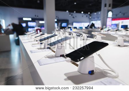 Smartphones On The Background Of The Electronics Store. Department Of Mobile Phones In The Tech Stor