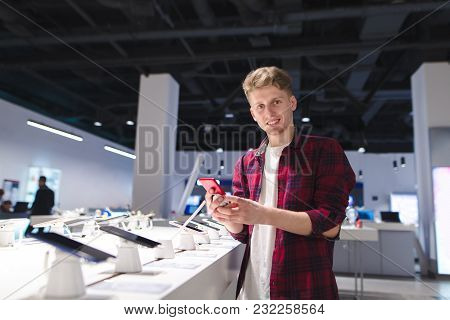 A Positive Young Man Stands In The Technology Store With A Phone In His Hands, Looks At The Camera A
