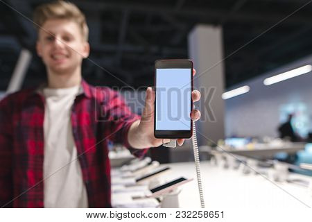 A Positive Young Man Sends A Smartphone With A White Screen To The Camera And Smiles. Young Man With