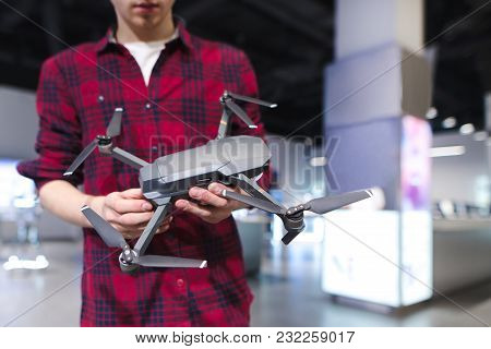 A man stands in a technology store and holds a quadcopter in his hand. Buying a quadcopter in the electronics store poster