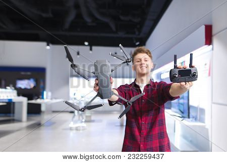 A Positive Young Man Holds A Quadcopter In His Hands And A Control Panel In The Background Of The St