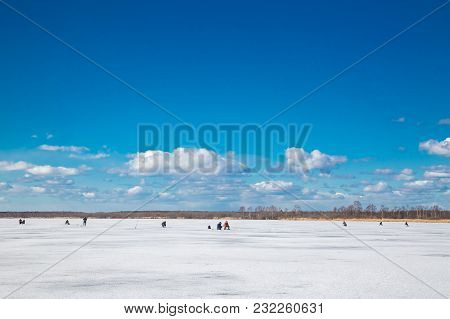 Fishermans Catching Fish On River In Winter