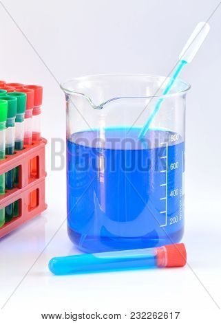 Glass Chemical Beaker With Blue Chemicals Dissolved In Water, Laboraty Pipette And Tube, Set Of Chem