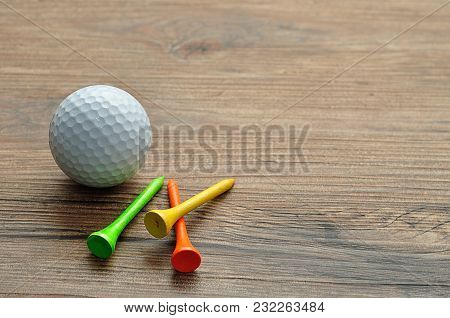 A Golf Ball With Tee's Isolated On A Wooden Background