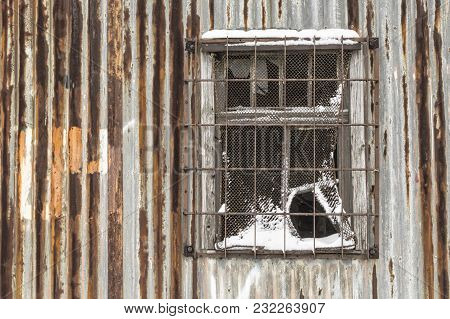 Rusty Corregated Metal Wall With Screened Window.