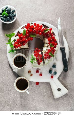 Bundt Cake With Fresh Berries And Sauce From Sour Cream On Grey Stone Table And Two Cups Of Espresso