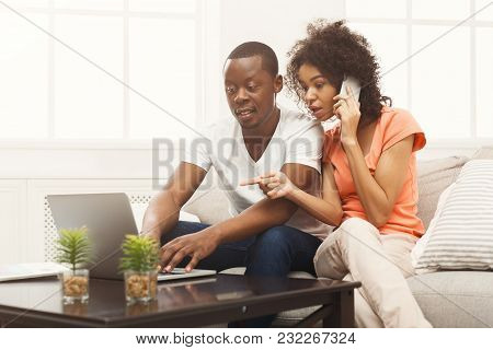 Young Couple Web Surfing On Laptop Sitting On Sofa At Home, Woman Talking On Phone, Relaxing. Freela