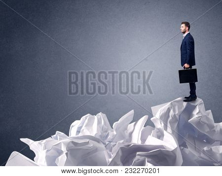 Thoughtful young businessman standing on a pile of crumpled paper