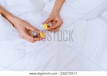 Girl Sits In Bed Under A White Blanket, Holds Yellow Ear Plugs Against Street Noise