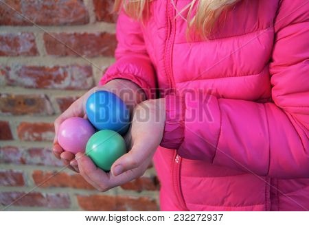 Young Girl Holding Easter Eggs.  A Little Girl With Blond Hair Holds Three Pastel Colored Easter Egg