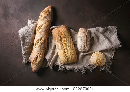 Variety Of Loafs Fresh Baked Artisan White And Whole Grain Bread On Linen Cloth Over Dark Brown Text