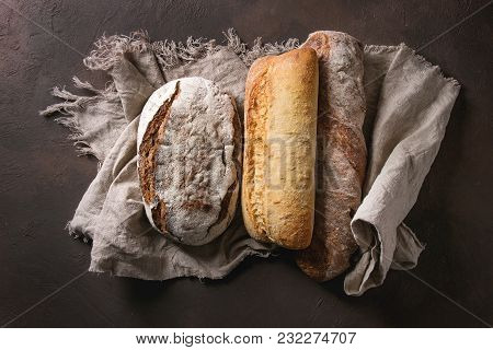 Variety Of Loafs Fresh Baked Artisan Rye, White And Whole Grain Bread On Linen Cloth Over Dark Brown