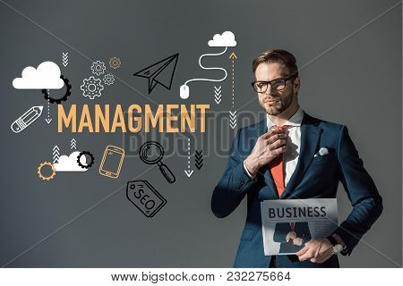Handsome Young Man In Eyeglasses Holding Newspaper And Adjusting Necktie, Managment Concept