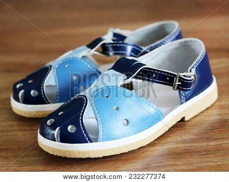 Blue Child's Sandals On Wooden Background