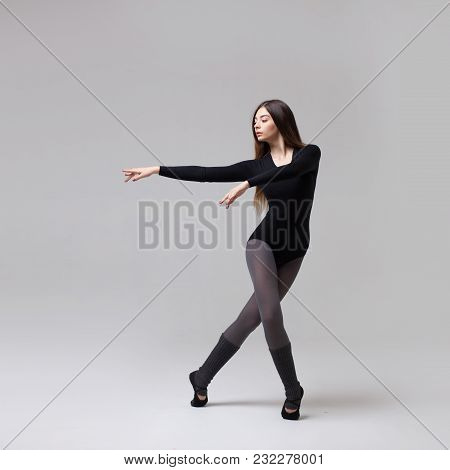 Young Beautiful Dancer With Long Brown Hair Wearing Black Swimsuit Posing On Light Grey Studio Backg