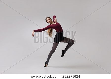 Young Beautiful Woman Dancer With Long Brown Hair Wearing Maroon Swimsuit Posing On A Light Grey Stu