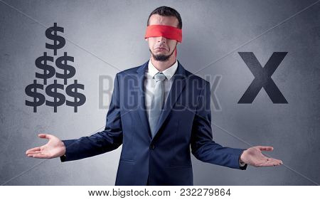 Serious businessmen standing in front of a grey wall with red ribbon on his eye, holding dollars