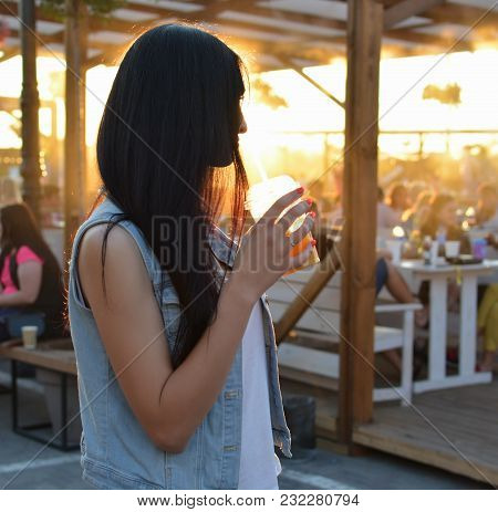 Portrait Of A Young Beautiful Dark-haired Woman In A Blue Denim Vest Drinking Orange Juice In A Summ
