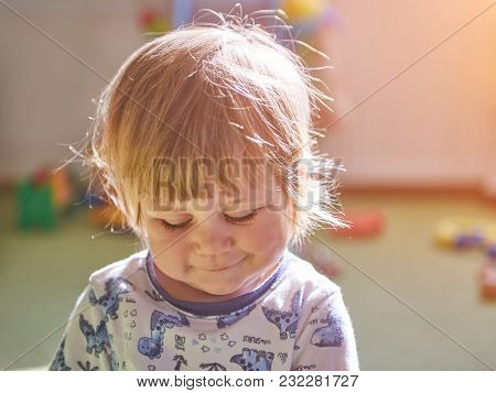 Portrait Of Cute Adorable Blonde Caucasian Smiling Baby Child Girl With Blue Eyes Sitting On Floor I