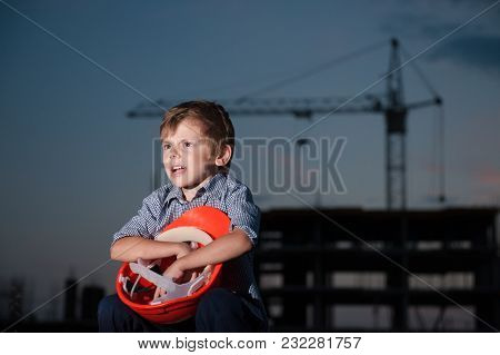 Screaming Boy Sitting With Orange Helmet In His Hands On Background Of Construction Site With Crane