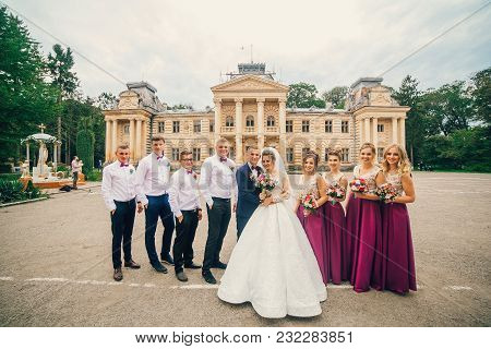 Wedding Of The Newlyweds. Cheerful And Fun Groom With Bride, Bridesmaids And Groomsmen Posing Outdoo