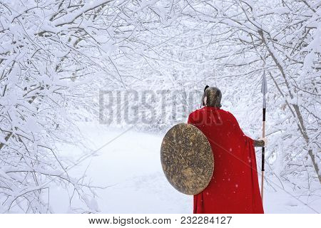 Careful Spartan In Cold Snowy Forest. A Man Looks Brave. He Keeps Traditional Spartan Armor: Round B