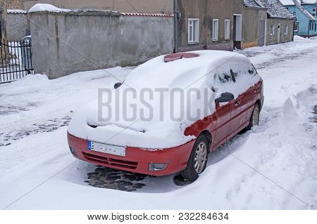 Car Covered With Snow. A Small Provincial Small Town. Low Buildings. Street Where A Red Passenger Ca