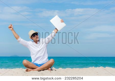 Lifestyle Young Asian Man Relaxing After Working On Laptop While Sitting On The Beautiful Beach, Fre