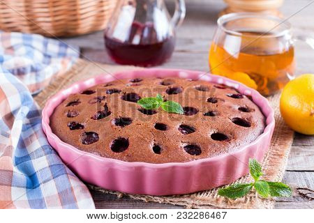 Chocolate Pie With Cherries In Ceramic Form On A Wooden Table