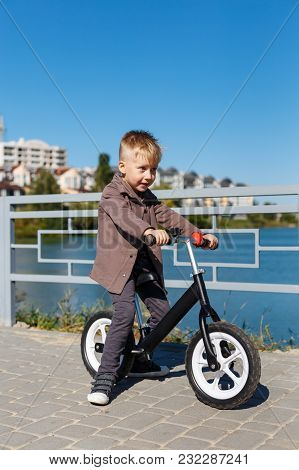 Happy Four Years Old Boy Riding Bicycle Without Pedals On The Background Of River And Buildings. Spo