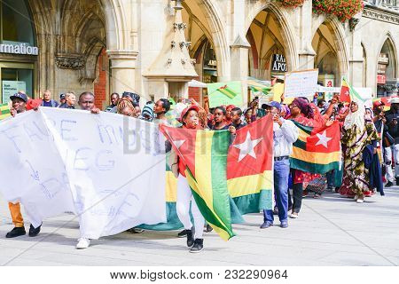 Munich, Germany - September 8 2017; Protesters Carrying Signs And Togo Flags March Through Tourists