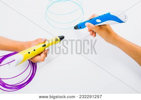 Kids Hands Holding Blue And Yellow 3d Pencils With Filaments On White Background. Top View