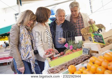 Senior people at the farmer's fresh market buying fruits and vegetables