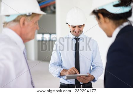 Satisfied Mixed Race Engineer In Helmet Examining Online Sketch On Tablet While Discussing Building