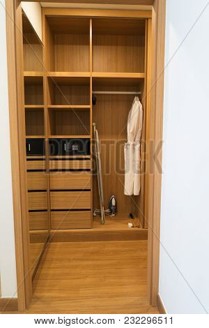 Dressing Room With Hanging Bathrobes, Ironing Board, Iron And Safe In Hotel Room. Spacious Walk-in C