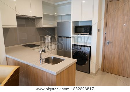 Home Appliances In Small Modern Kitchen. Corner Counter With Electric Stove, Sink And Cooker. Freeze