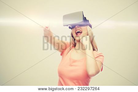 3d technology, virtual reality, entertainment and people concept - happy young woman with virtual reality headset or 3d glasses playing game and fighting over gray background and laser light