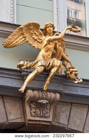 A Golden Winged Figure With A Wreath And A Cornucopia In Its Hands