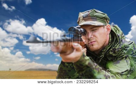 hunting, army, military service and people concept - young soldier, sniper or hunter with gun aiming or shooting over natural background and blue sky